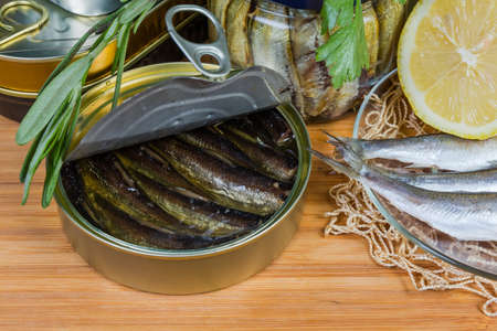 Smoked sprats in cooking oil in the open tin can among other canned fish, raw fish, greens on a wooden surface close-up in selective focus