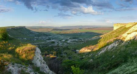 Plateau avec roche calcaire escarpée sur les bords et vallée sur fond de ciel, vue panoramique depuis le sommet d'un mont