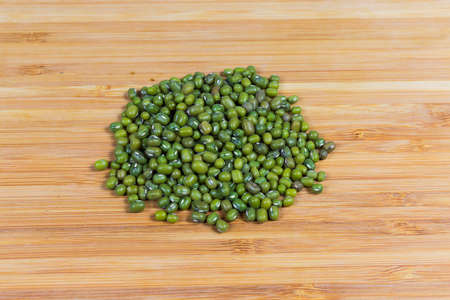 Small pile ripe whole mung beans on a bamboo wooden surface Фото со стока