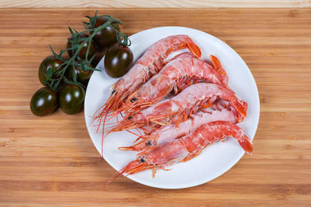 One frozen ocean king prawn and several usual shrimps on dish, cluster of the fresh cherry tomato kumato on a wooden surface, top view