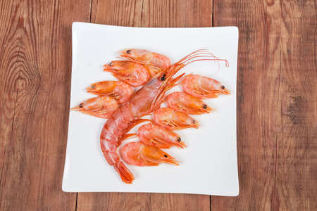 One ocean king prawn and several usual shrimps on square dish on the wooden rustic table, top view Фото со стока