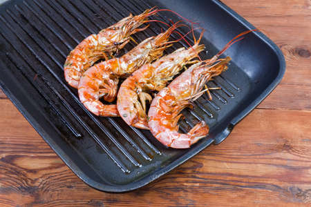 Grilled wild Argentinian red shrimps with heads on the grill pan on the wooden rustic table Фото со стока