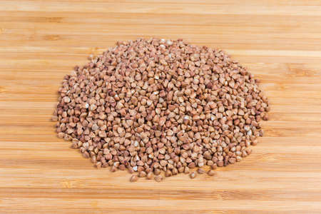 Pile of uncooked brown pre-steamed wholegrain buckwheat groats close-up on a bamboo wooden cutting board