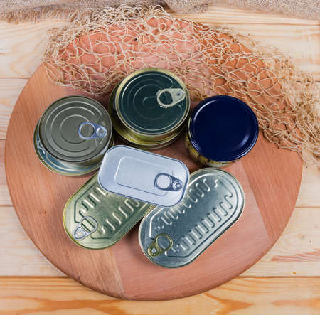 Various types of sealed tin cans and glass jar of canned fish on the round wooden service board, top view