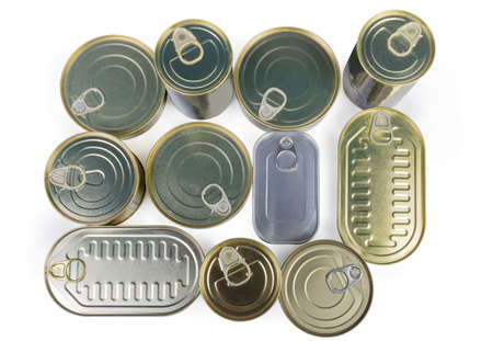 Set of canned fish and seafoods in various types of sealed tin cans on a white background, top view