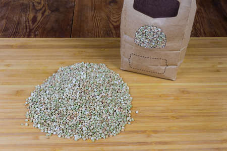Pile of the uncooked green not steamed wholegrain buckwheat groats and paper bag of the same group on wooden cutting board on the rustic table