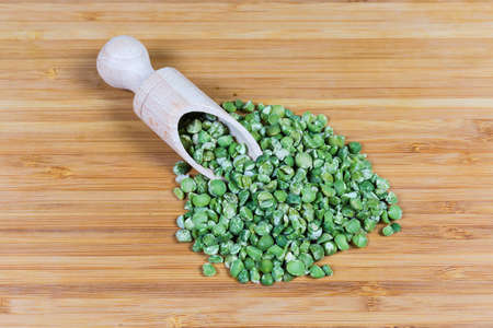 Ripe split peas of green variety in wooden spice spoon and scattered beside her on a bamboo wooden surface, top view Фото со стока