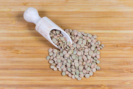 Ripe whole brown lentil in wooden spice spoon and scattered beside her on a bamboo wooden surface Фото со стока