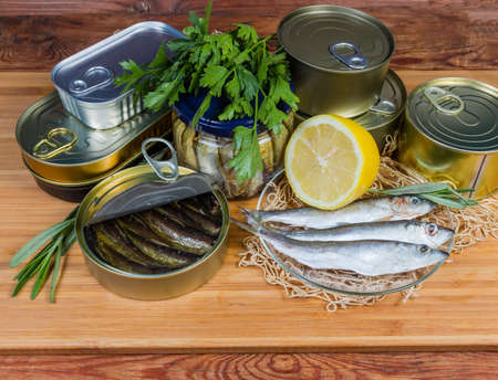 Smoked sprats in cooking oil in the open tin can among of sealed cans and glass jar of canned fish, raw fish greens and lemon on a wooden surface Фото со стока