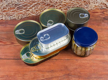 Set of canned fish and seafoods in glass jar and various sealed tin cans on the old rustic table Фото со стока