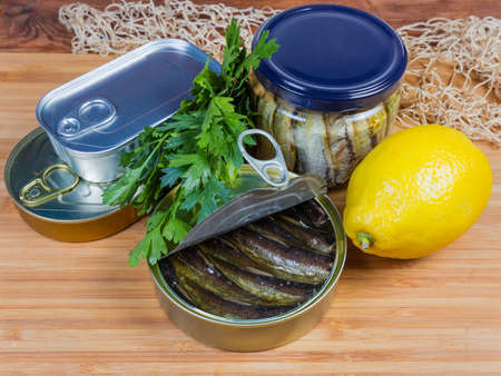 Smoked sprats in cooking oil in the open tin can against of sealed cans and glass jar, greens and lemon on a wooden surface