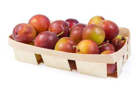 Fresh ripe plums in small wooden basket on a white background Zdjęcie Seryjne