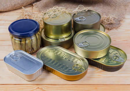 Set of canned fish and seafoods in various types of sealed tin cans and glass jar on the rustic table