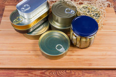 Set of canned fish and seafoods in glass jar and various sealed tin cans on a wooden surface