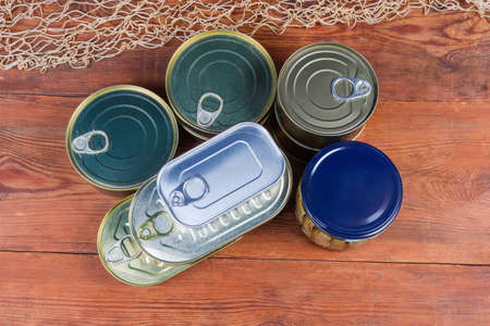 Various types of sealed tin cans and glass jar of canned fish on the old wooden rustic table, top view