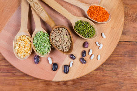 Various raw legumes - yellow and green split peas, red and brown lentils and mung beans in the wooden spoons and scattered kidney beans beside to them on wooden surface, top view