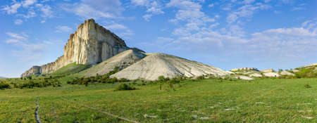 Steep white limestone rock on edge of the plateau on a background of sky, panoramic view