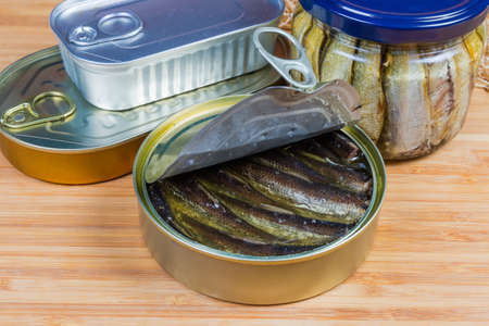 Smoked sprats on cooking oil in the open tin can against of other canned fish on a wooden surface close-up in selective focus