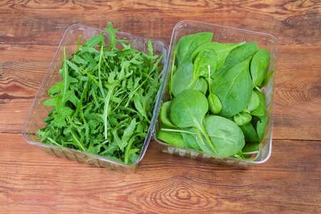 Leaves of fresh arugula and spinach in two different transparent plastic containers on the old rustic table, top view