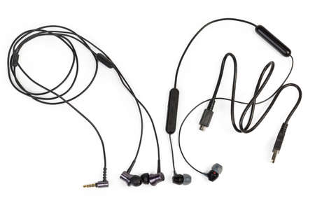 Two pair of black in-ear earphones - wireless with USB cable to charge the battery and wired with typical audio connector on a white background, top view