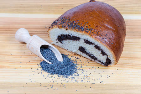 Raw blue poppy seeds in the special wooden spice spoon and scattered beside her, pie with sweet crushed poppy seed filling and sprinkled with whole poppy seeds on wooden surface Stock Photo