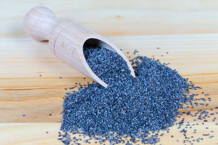 Edible blue poppy seeds in the special wooden spice spoon and scattered beside her on the wooden surface close-up in selective focus Stock Photo