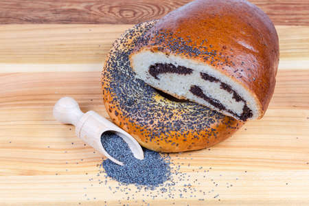 Raw blue poppy seeds in the special wooden spice spoon and scattered beside her, pie with sweet crushed poppy seed filling, big bagel sprinkled with poppy seeds on wooden surface Stock Photo