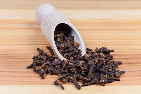 Whole dried cloves in the special wooden spice spoon and scattered beside her on the wooden surface close-up in selective focus Stock Photo