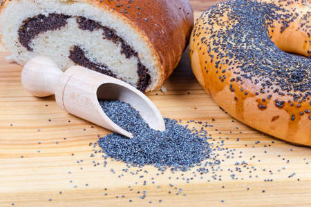 Raw blue poppy seeds in the special wooden spice spoon on background of pie with crushed poppy seed filling and big bagel sprinkled with poppy seeds on wooden surface