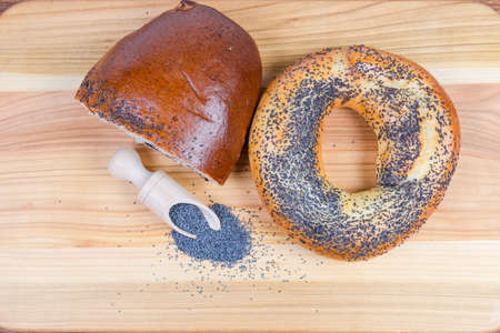 Raw blue poppy seeds in the special wooden spice spoon, pie with crushed poppy seed filling and big bagel sprinkled with poppy seeds on wooden surface, top view