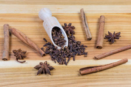 Whole dried cloves in the wooden spice spoon, star anise fruits and cinnamon sticks on the wooden surface