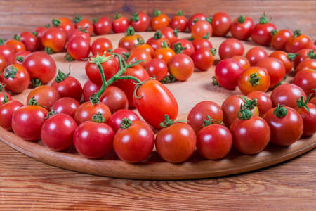 Cherry tomatoes laid out on the round wooden serving board on the rustic table, fragment close-up in selective focus