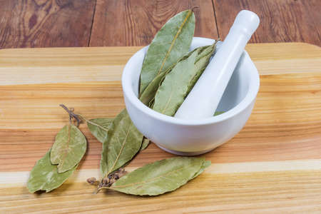 Whole dried bay leaves in porcelain kitchen mortar with pestle, small bay twigs with leaves on the wooden cutting board on rustic table