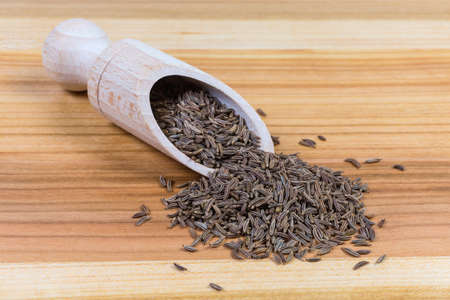 Whole caraway seeds in the special wooden spice spoon and scattered beside her on the wooden surface close-up in selective focus Stock Photo