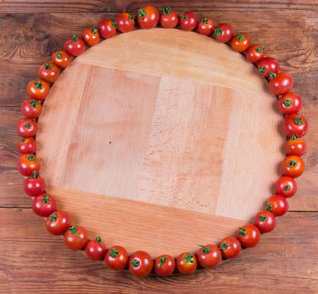 Cherry tomatoes laid out around the perimeter of round wooden serving board with empty remaining part on the rustic table, overhead view, background