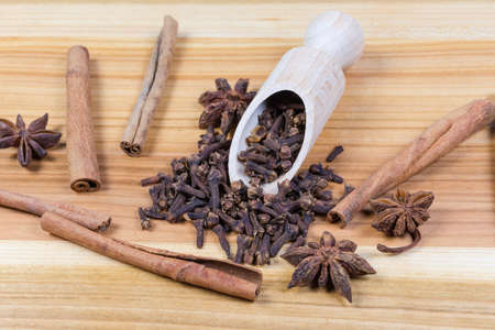 Whole dried cloves in the wooden spice spoon, star anise fruits and cinnamon sticks on the wooden surface close-up in selective focus