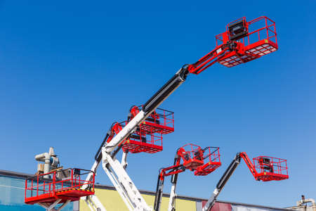 Fragment of the booms with baskets and top parts of different articulated boom lifts and scissor lifts on a background of clear sky 스톡 콘텐츠