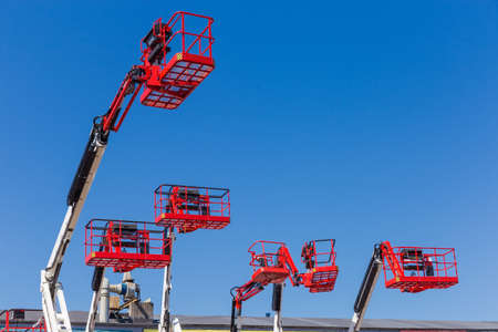 Red baskets on the white booms of different articulated boom lifts and top parts of lifts on a background of clear sky Stockfoto