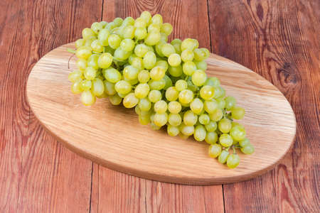 Cluster di mature bianco uva senza semi sultana varietà, noto anche come Thompson Seedless sull'ovale in legno che serve bordo sul tavolo rustico