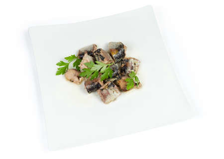 Pieces of the canned fish in its own juice with cooking oil addition, decorated with parsley on dish on a white background