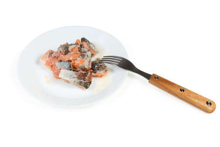 Pieces of the canned salmon in its own juice on dish with fork on a white background