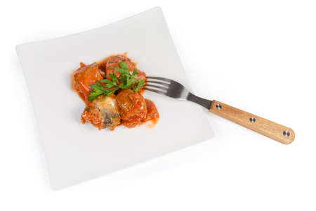 Pieces of the canned fish in tomato sauce, fresh parsley twig on the white square dish with fork on a white background