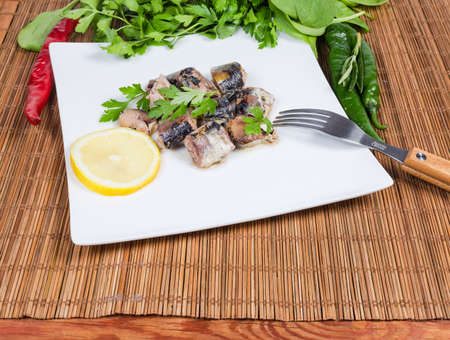 Pieces of the canned fish in its own juice, parsley and lemon slice on white dish with fork among vegetables and greens on the bamboo table mat Banco de Imagens