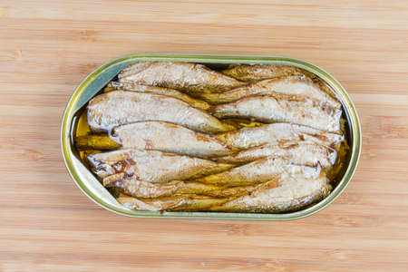 Smoked canned sprats in cooking oil in open tin can on a wooden surface, top view