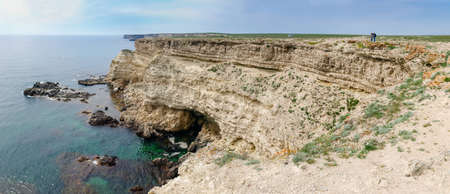 Steep textured limestone rocks, which break off to the water of the flat sea shore, panoramic view