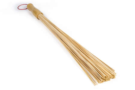 Big wooden massage broom, made of bunch of thin natural bamboo rods on a white background, close-up in selective focus