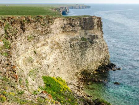 Steep textured limestone rocks along the coastline on the flat sea coast on a background of sea 스톡 콘텐츠