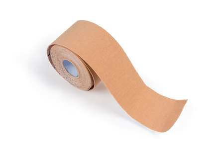Roll of the flesh-colored elastic therapeutic tape, also known as kinesiology tape on a light background