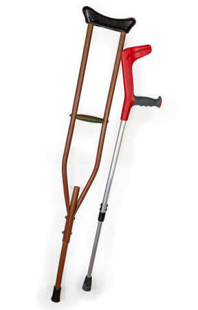 One modern elbow crutch with comfy ergonomic handle and one old underarm crutch on a white background