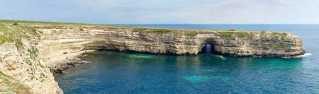 Promontory protruding into the sea with sheer textured limestone rocks and natural through grotto on the sea shore, wide panoramic view